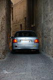 Car almost get stuck. In Toledo car drivers have to pay special attention when driving in a tight street so that their vehicles do not get stuck royalty free stock photo