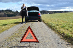 Car, girl and warning triangle Stock Images
