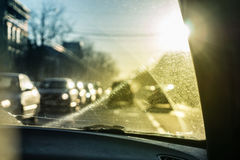 Car glass with unclean texture. Blurred road on background. Morning sunlight. Stock Photo