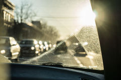 Car glass with unclean texture. Blurred road on background. Morning sunlight. Stock Images