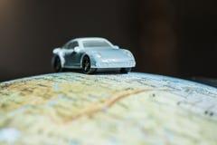 Car on globe. Car figure on globe. Miniature car toy Royalty Free Stock Image