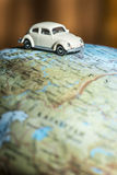 Car on globe. Car figure on globe. Miniature car toy Stock Images