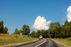 The car goes on highway in the middle of trees Royalty Free Stock Images