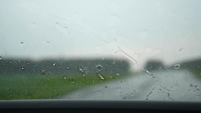 The car goes on the highway. It is raining hard outside, windscreen wipers are working. Raindrops on glass. The car goes on the highway. Raindrops on glass. It stock video