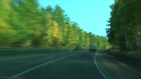 Car goes on the road quickly. View of the car riding fast on a country road stock footage