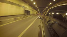 The car goes through the tunnel in heavy traffic. Side view from the car body. The car goes through the tunnel in heavy traffic. Side view stock footage