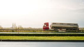 Car going fast on raining scenery. Big tank truck going fast in raining and sunny day Royalty Free Stock Photography
