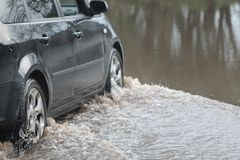 Car Going Through Flood. Car forcing a way through a flood on the River Ritec near Tenby, Pembrokeshire, UK stock photos