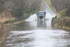 Car Going Through Flood. Car forcing a way through a flood on the River Ritec near Tenby, Pembrokeshire, UK stock image