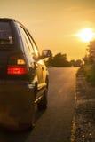 Car going toward sunset through countryside Stock Images