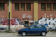 Car and graffiti. Lancia Ypsilon parked in front of an industrial building with graffiti. Rome, Italy Royalty Free Stock Images