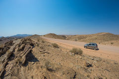 Car on gravel road in the Namib desert, Namib Naukluft National Park, main travel destination in Namibia, Africa. Concept of peopl Royalty Free Stock Images