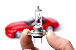 Car halogen light bulb and red car Royalty Free Stock Photos