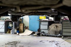 Car hanged on lift at sevice station. Dirty vehicle  maintenace center. Disorder, mud, stains and chaos. Unprofessional clumsy aut. Omobile workshop Royalty Free Stock Photos