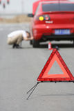 Car has broken down. Young man sends a warning sign by a red car Royalty Free Stock Images