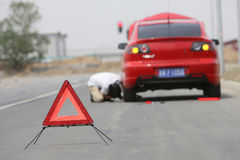 Car has broken down. Young man sends a warning sign by a red car Royalty Free Stock Photos