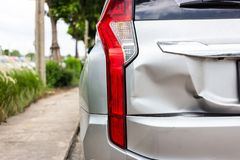 A car has a dented rear bumper after an accident,Backside of new. Silver car get damaged stock images