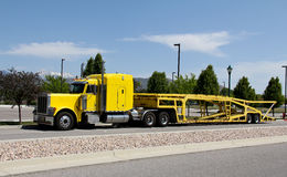 Car Hauler. Image of a yellow semi truck with a car hauler trailer Stock Photo