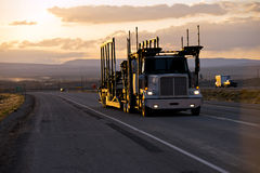 Car hauler semi truck on the road in sunset. The big rig powerful semi truck with a car hauler trailer for the transporting of cars on the straight road in the Royalty Free Stock Photos