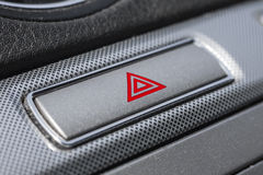 Car hazard warning button. Car hazard warning flashers button with visible red triangle. Red hazard in car interior stock images