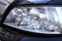 Car headlight. Shiny headlight of black car stock photo