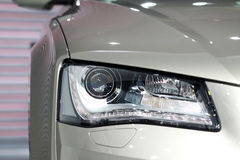 Car Headlight. Headlight of a silver car royalty free stock image