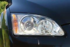 Car headlight. Black car's headlight close up Royalty Free Stock Photography
