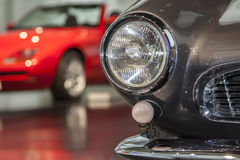 Car headlight in the background of red car. Part of car in the background of red car Royalty Free Stock Photography