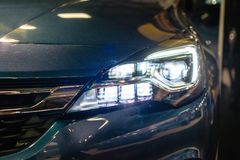 Car headlight with backlight. Exterior detail.Dark color car - image stock image