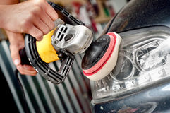 Car headlight cleaning with power buffer machine. At service station Stock Photography