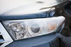 Car headlight covered with snow. Stock Photography