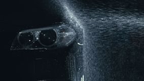 Car headlight wash. Washing modern vehicle body by high pressure jet wash hose water. Auto glass headlamp, angel eyes in