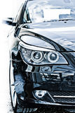 Car headlights. Black car front bumper and headlights with xenon bulbs royalty free stock photography
