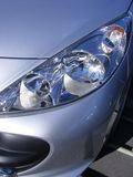 Car headlights. Lights to light gray car for safe driving Stock Image