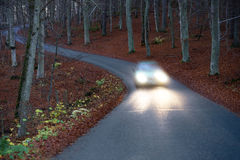 Car with headlights on country road Royalty Free Stock Photo