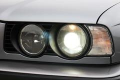 Car headlights. Luxury Headlights. Gray car royalty free stock image