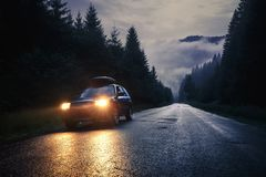 Car with headlights on at night road. Lviv, Ukraine - August 01, 2018: Car with headlights on at night road in mountains. Travel background royalty free stock images