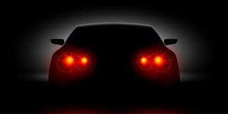 Car headlights shining in the dark back view Stock Photography