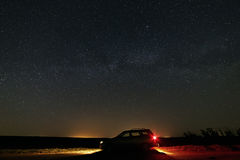 The car with the headlights switched on the background Milky Way. The car with the headlights switched on the background of the Milky Way in the starry sky Royalty Free Stock Photos