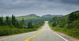 Car on a Highway through coastal Foothills of Newfoundland. Newfoundland highway in overcast skies. Lone car goes down the road. Coastal highways in foothills royalty free stock image