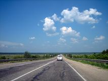 The car highway in the cracks goes far into the distance on a bright Sunny day royalty free stock image