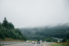 Car on highway in foggy weather. Asphalt highway with cars on the road and green forest on the background in a fog, Germany stock image