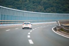 Car on the highway with noise barrier. Rear view of car driving on the highway with noise barrier stock image