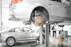 Car on the hoist at the car service. Car standing on the hoist during the diagnostics at the car service stock photo