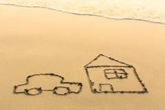 Car and a house drawn on the sand beach Royalty Free Stock Photos
