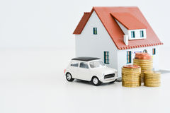 Car and house model with stack of coins isolated on white background Royalty Free Stock Image