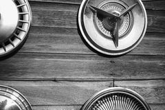 Car hubcaps hanging on aged wood wall. Old car Hubcaps shot in black and white hanging on wood wall royalty free stock image