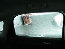 Car Ice Scraping. Young man scraping ice off a car window as seen from inside the car Royalty Free Stock Photos