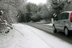 Car on icy road. Silver car driving on an icy road, on a snowy day Stock Images