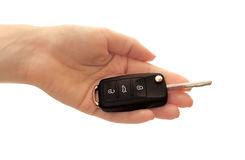 Car ignition key on woman hand over white background. Car ignition key in woman hand over white background. Closeup of black car key in hand isolated on white Stock Images